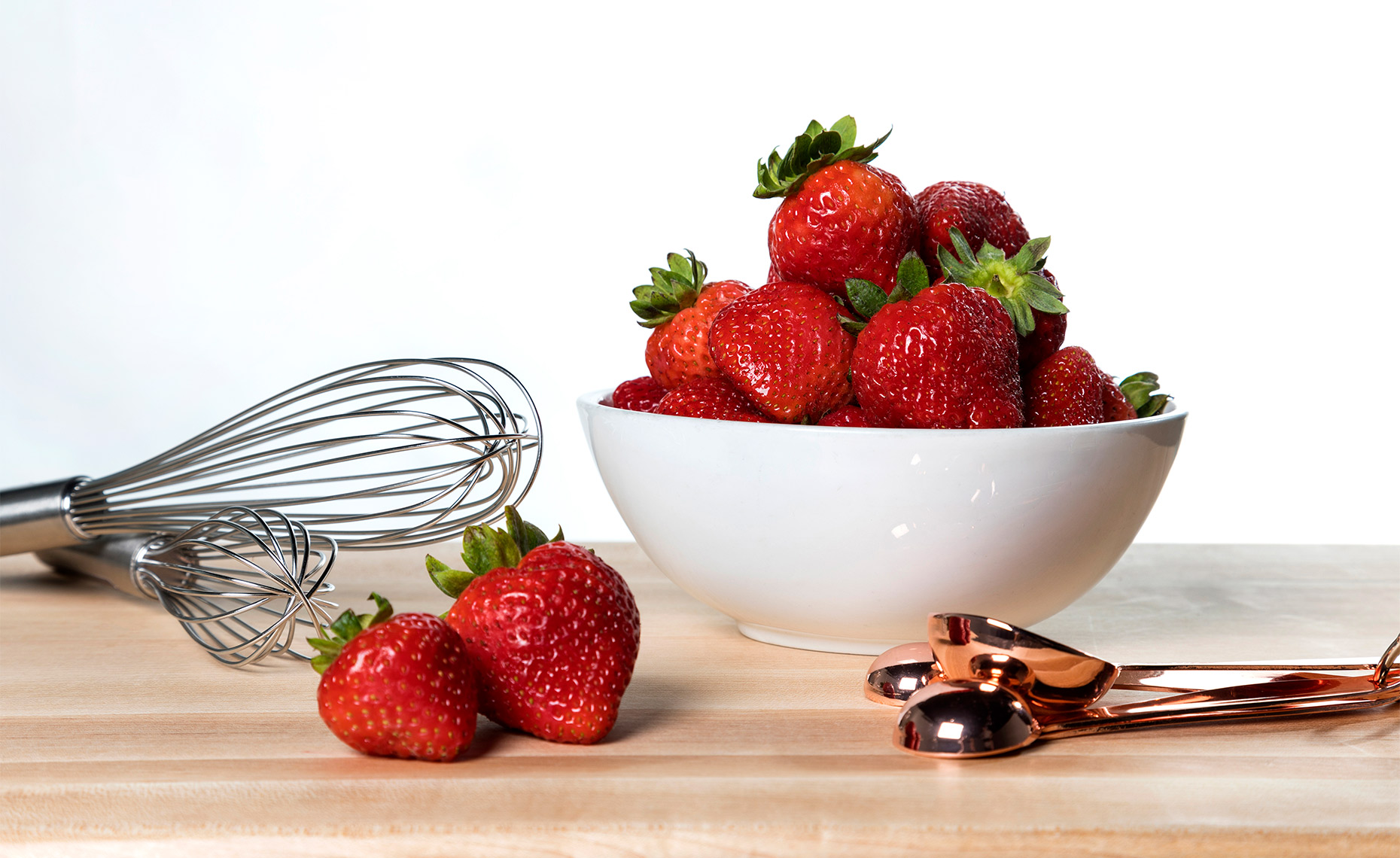 Strawberries in a ceramic white bowl.