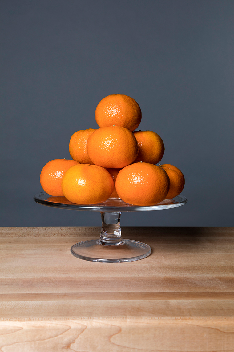 Tangerines on a glass stand.